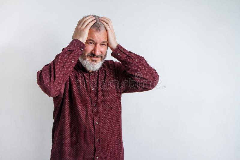 Grijs-haired mens met een baard die aan wanhopig en beklemtoonde hoofdpijn lijden omdat pijn en migraine royalty-vrije stock fotografie