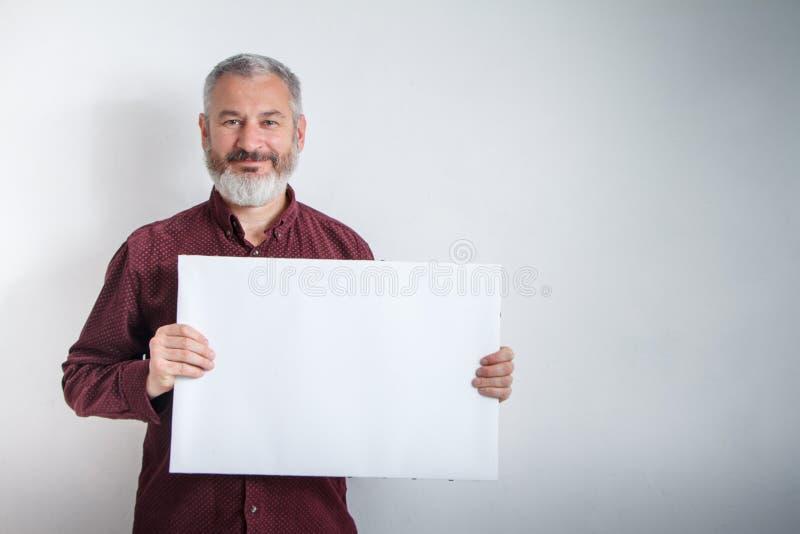 Grijs-haired mens met een baard die wit leeg uithangbord met ruimte voor tekst voor hem houden royalty-vrije stock fotografie