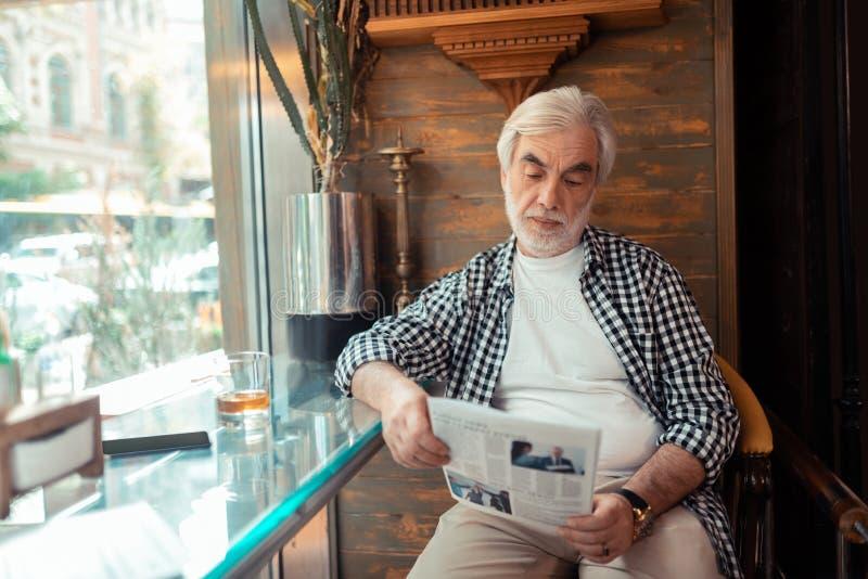 Grijs-haired mensenlezing nieuws en het drinken wisky stock foto's