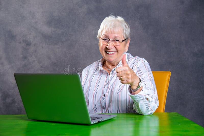 Grijs harig bejaarde met duim die PC uitputten royalty-vrije stock afbeeldingen