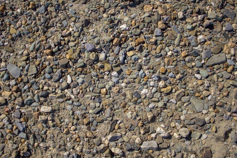 Grijs-witte blauwe gele stenen van verschillende grootte en vormen op het lichte zand ruwe natuurlijke oppervlaktetextuur stock foto's