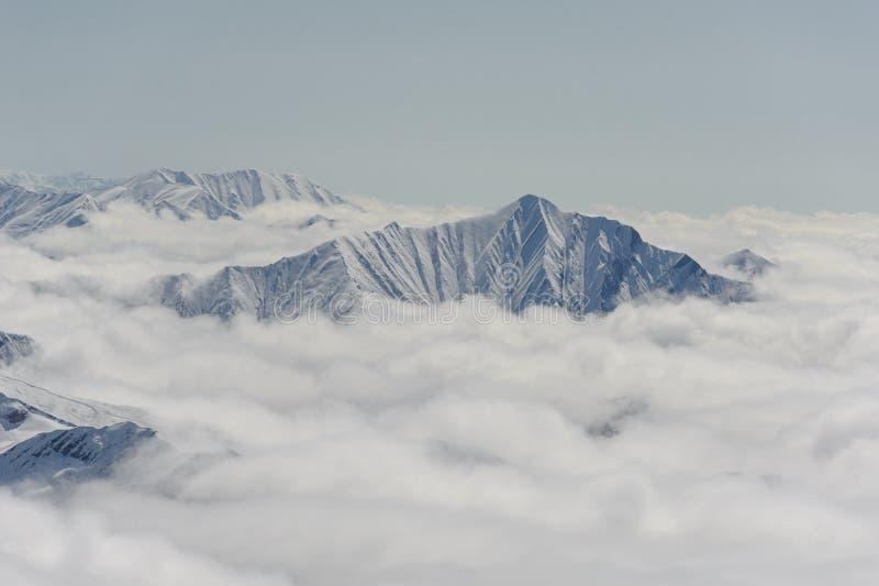 Grijs-witte die bergen in de sneeuw, in wolken wordt gehuld royalty-vrije stock foto