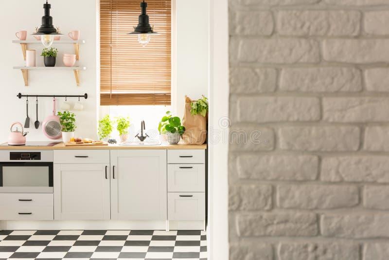 Grijze bakstenen muur in helder keukenbinnenland met lampen boven coun stock foto