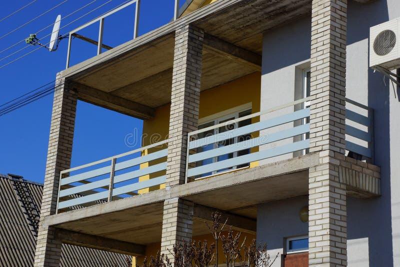 Grijze balkonportiek van raad en bakstenen op de voorgevel van het huis stock afbeelding