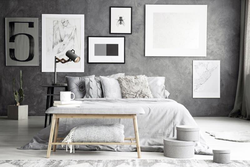 Grijze bank in elegante slaapkamer stock afbeelding