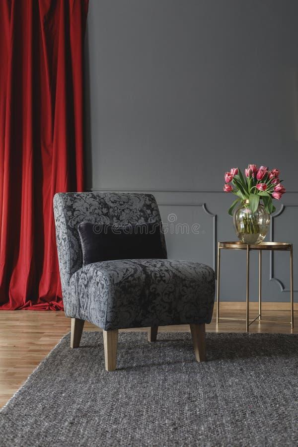 Grijze bloemenstoel met zwart kussen die zich op donker tapijt in elegant ruimtebinnenland bevinden met verse tulpen op gouden me royalty-vrije stock afbeelding