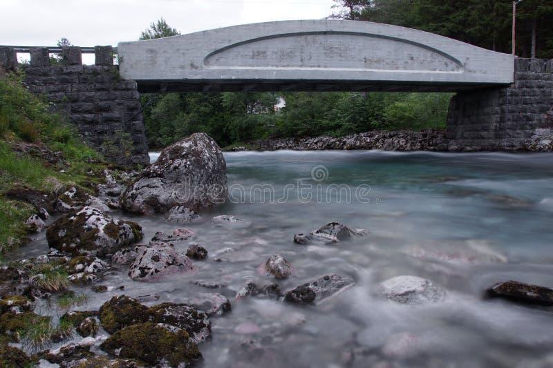 Grijze concrete brug over een schone blauwe rivier in Noorwegen stock foto