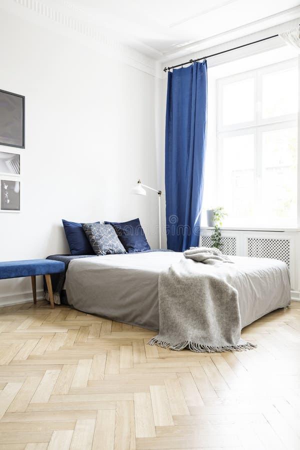 Grijze deken op bed in helder slaapkamerbinnenland met lamp en marineblauw gordijn bij venster Echte foto stock foto