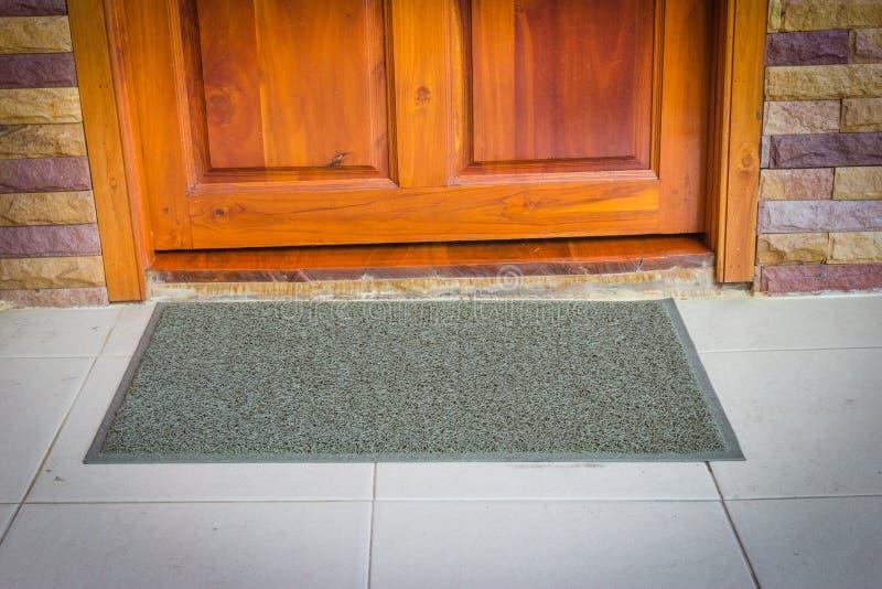 Grijze deurmat met dichte deur stock fotografie