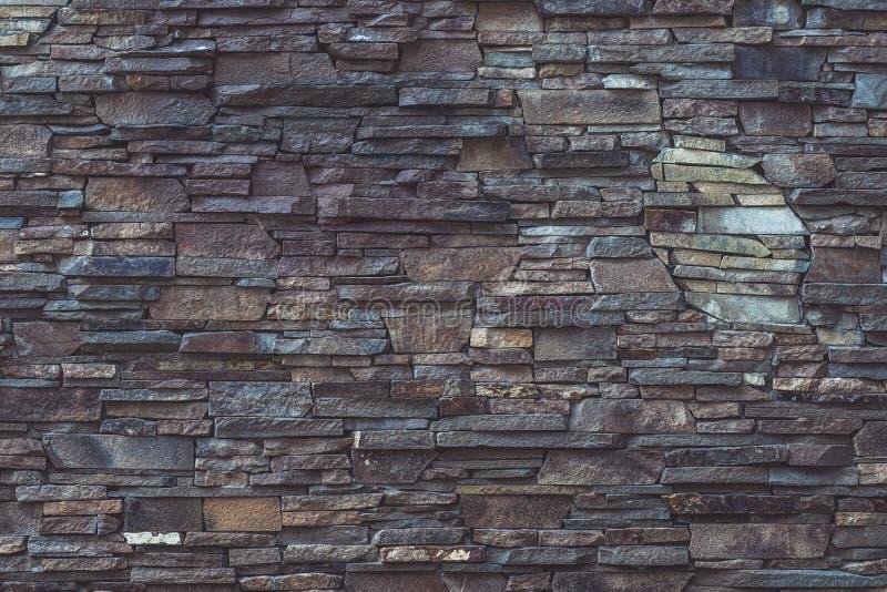 Grijze en bruine dilapidated steentextuur van de voorgevelbouw Ruw metselwerk, vuile doorstane, grijze dilapidated muurachtergron royalty-vrije stock foto