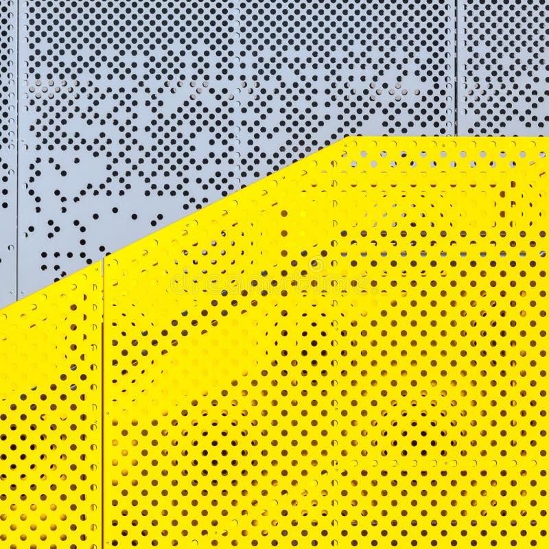 Grijze en gele geperforeerde industriële metaalachtergrond royalty-vrije stock afbeelding