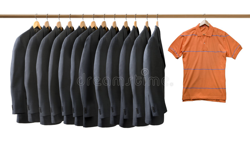Grijze gehangen jasjes en oranje t-shirt stock fotografie