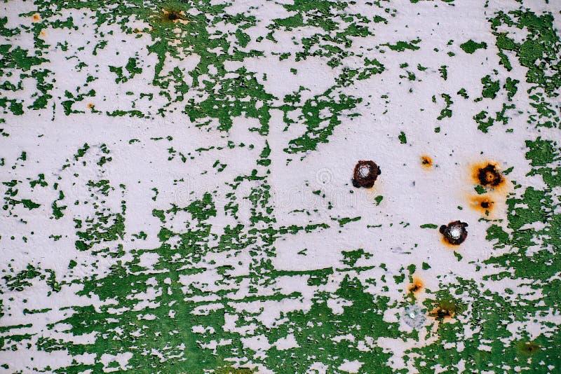 Grijze geschilderde metaalmuur met gebarsten groene verf, roestvlekken, blad van roestig metaal met gebarsten en vlokkige groene  royalty-vrije stock foto's