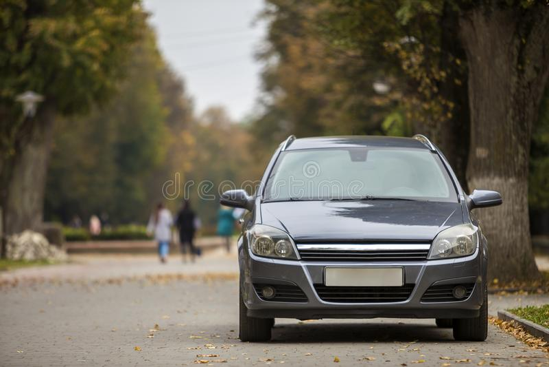 Grijze glanzende die auto op stil gebied op asfaltweg wordt geparkeerd op vage bokeh achtergrond op heldere zonnige dag Vervoer e royalty-vrije stock afbeeldingen