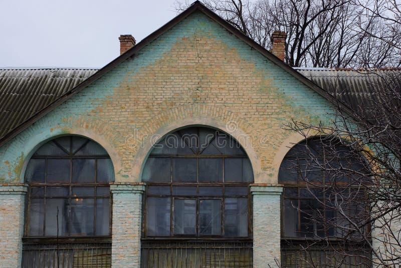 Grijze groene baksteenzolder van een oud huis met grote vensters stock afbeelding