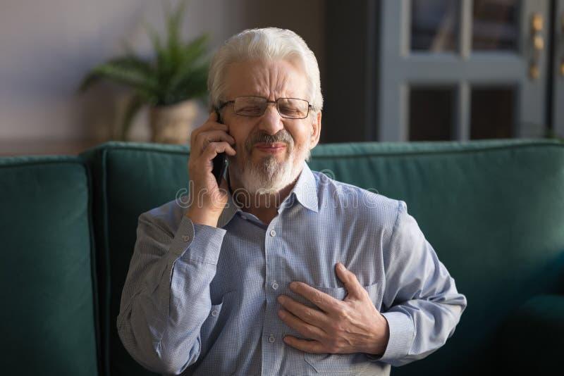 Grijze haired mens wat betreft borst, die hartaanval hebben, die noodsituatie roepen stock afbeelding