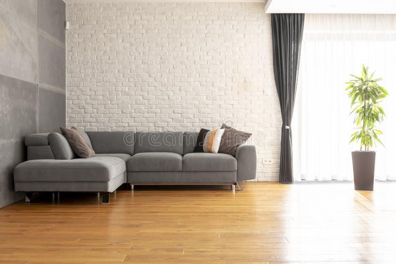 Grijze hoeklaag op houten vloer tegen bakstenen muur in heldere a royalty-vrije stock afbeelding
