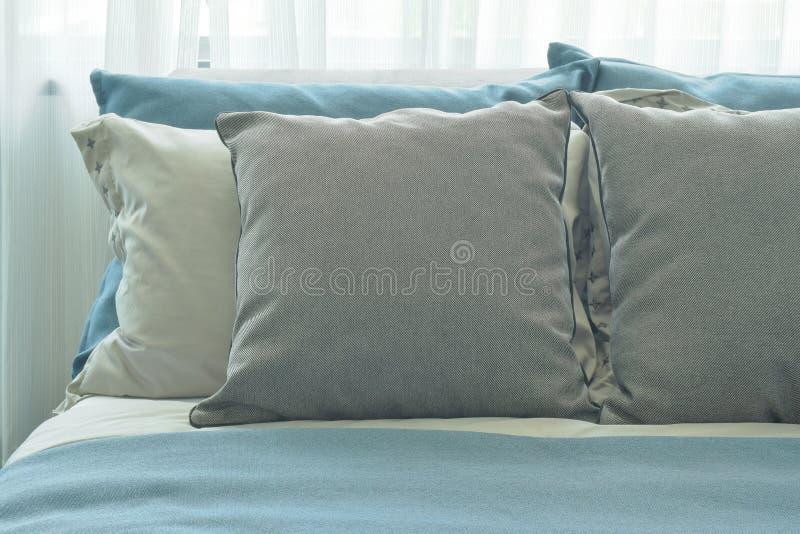 Grijze hoofdkussens die op blauw kleurenschemabeddegoed thuis plaatsen stock foto