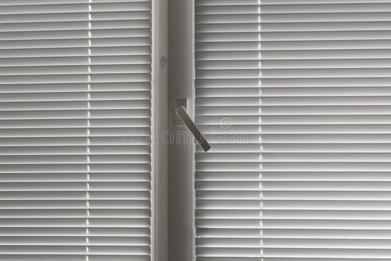 Grijze horizontale jaloezie in venster stock afbeeldingen