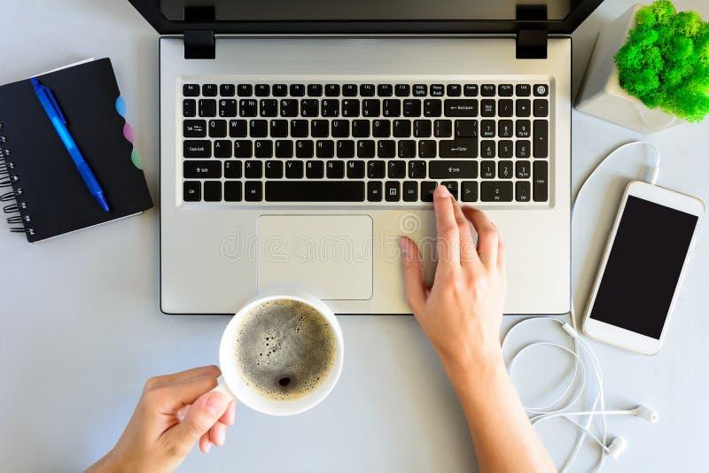 Grijze houten bureaulijst met laptop computer, smartphone, notitieboekje, pen en kop van koffie Vrouwelijke handen die laptop met stock fotografie