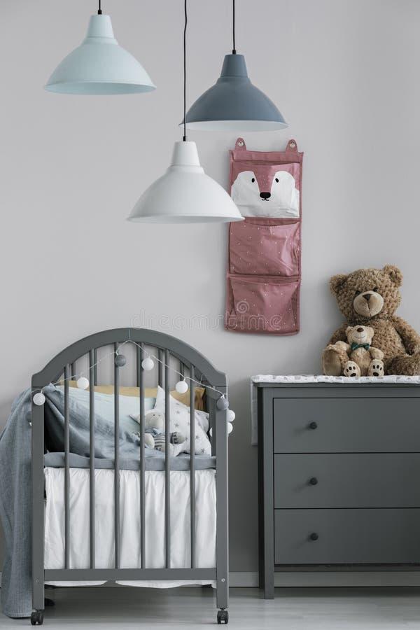 Grijze houten voederbak in het modieuze Skandinavische binnenland van de babyslaapkamer stock fotografie