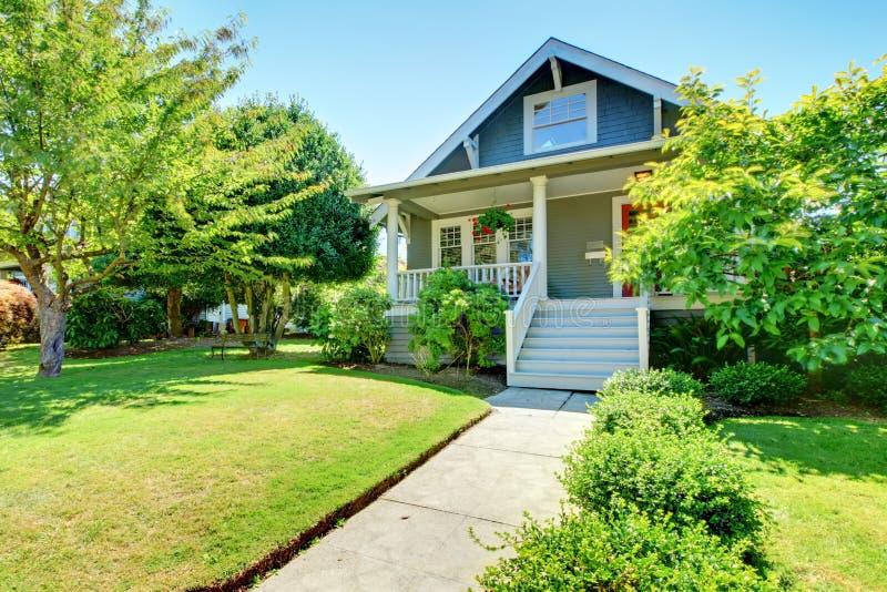 Grijze kleine oude Amerikaanse huisvoorzijde buiten met witte trap. royalty-vrije stock foto