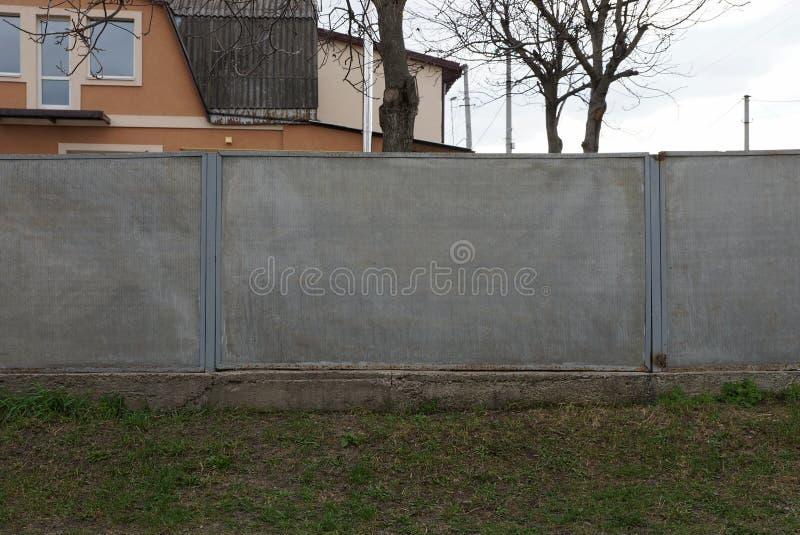 Grijze lange concrete omheining buiten in groen gras stock afbeeldingen