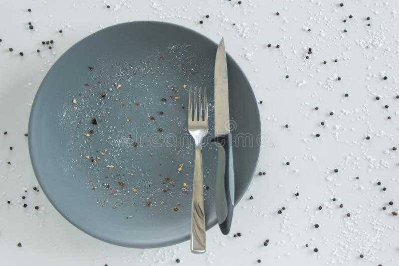 Grijze lege ceramische plaat met mes en vork op witte achtergrond met zout en peper Minimaal ontwerp Ruimte voor tekst stock foto's