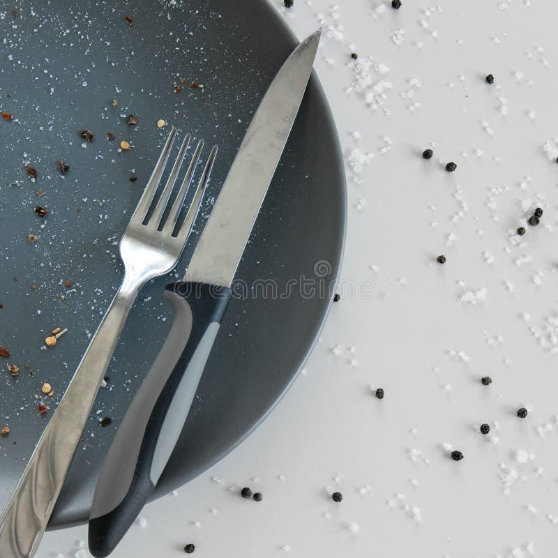 Grijze lege ceramische plaat met mes en vork op witte achtergrond met zout en peper Minimaal ontwerp Ruimte voor tekst stock foto