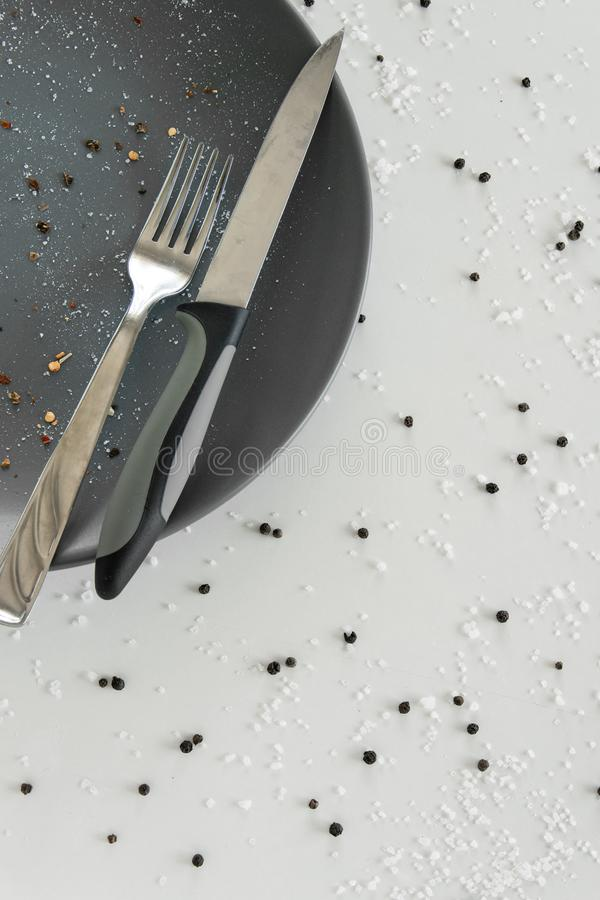 Grijze lege ceramische plaat met mes en vork op witte achtergrond met zout en peper Minimaal ontwerp Ruimte voor tekst stock fotografie