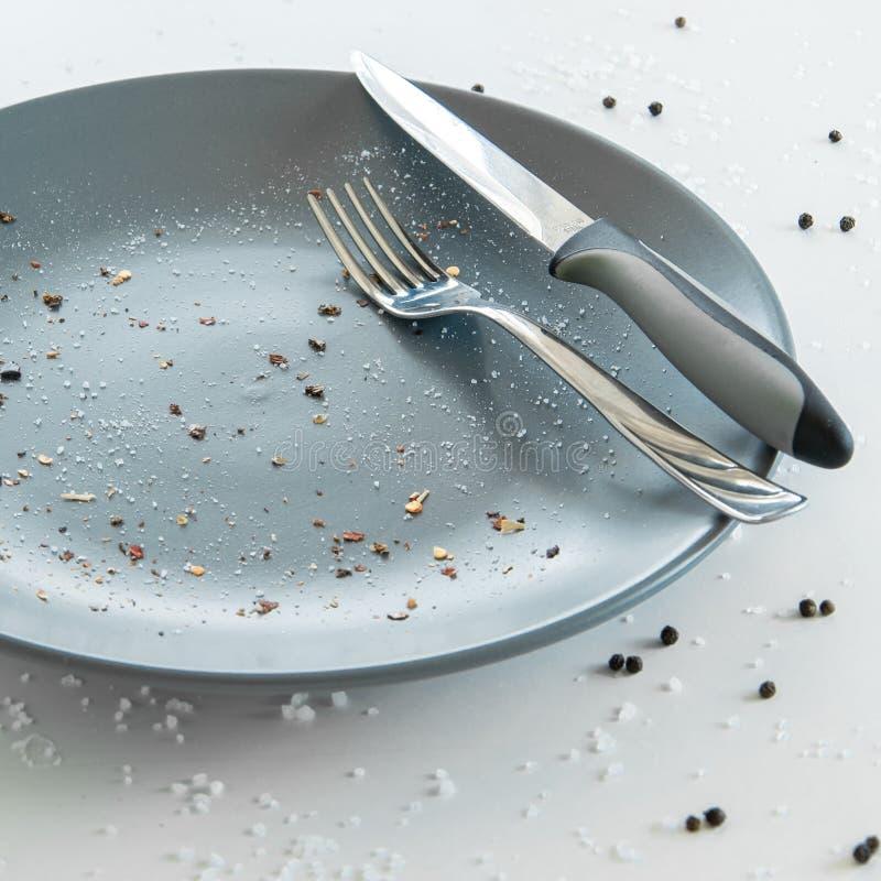 Grijze lege ceramische plaat met mes en vork op witte achtergrond met zout en peper Minimaal ontwerp Ruimte voor tekst royalty-vrije stock fotografie