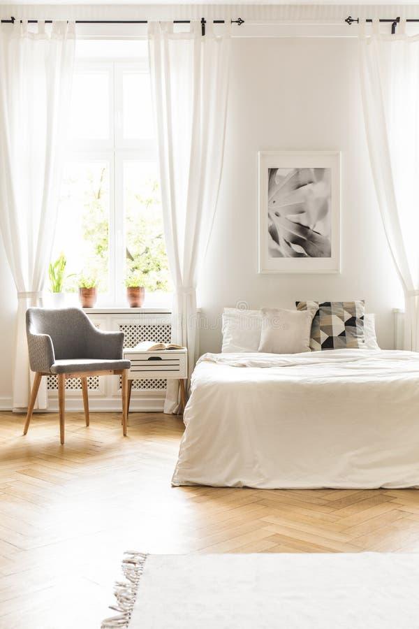 Grijze leunstoel bij venster met gordijn in witte slaapkamer binnenlandse wi stock afbeelding