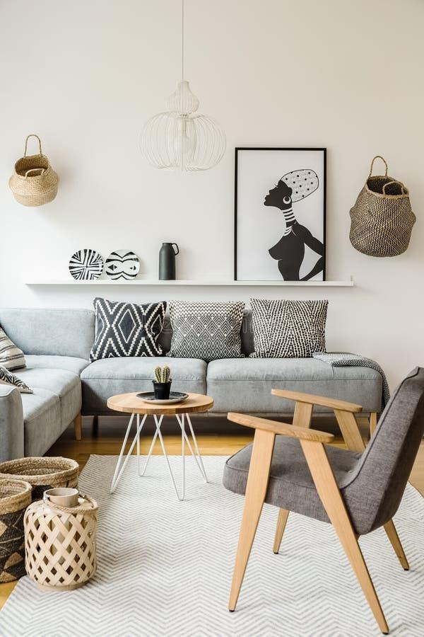 Grijze leunstoel naast houten lijst in helder binnenland met post royalty-vrije stock foto's