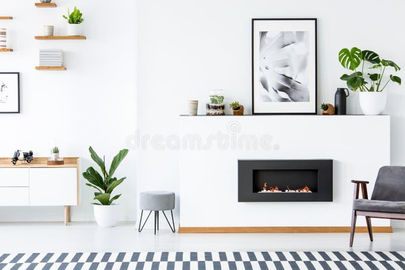 Grijze leunstoel naast open haard in het kader van affiche in woonkamer inte stock afbeeldingen