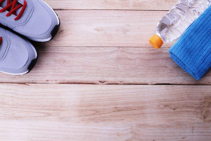 Grijze loopschoenen met geschiktheidstoebehoren op houten achtergrond stock foto's