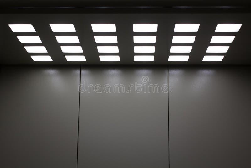 Grijze metaallift met vierkante lampen in het plafond royalty-vrije stock afbeelding