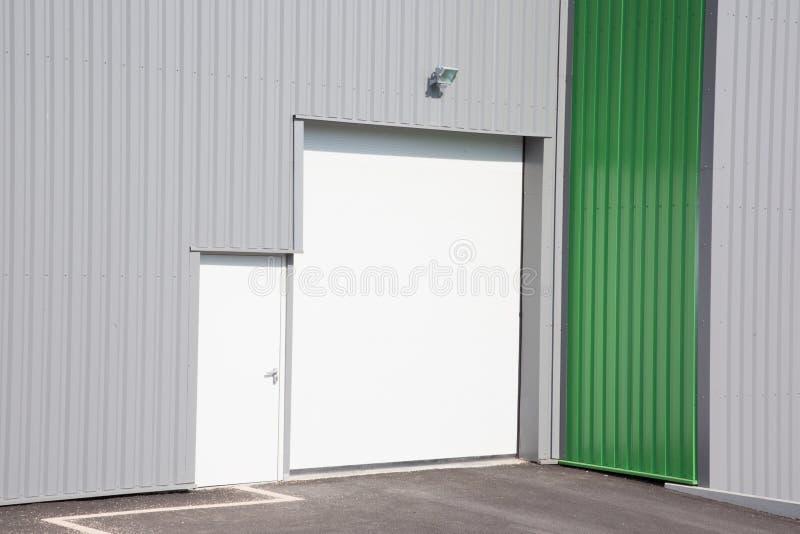grijze moderne industriële eenheid met roldeuren stock afbeeldingen