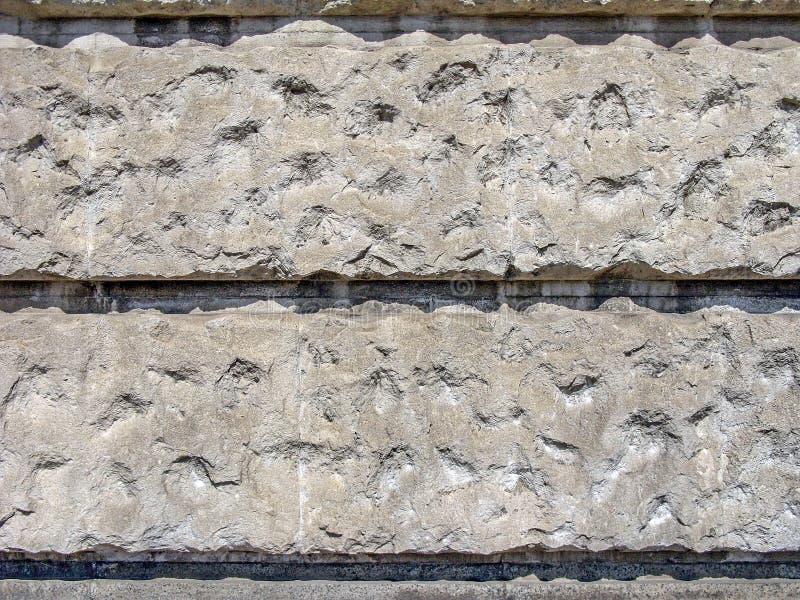 Grijze muur van concrete blokken met tekens van schade fragment stock foto