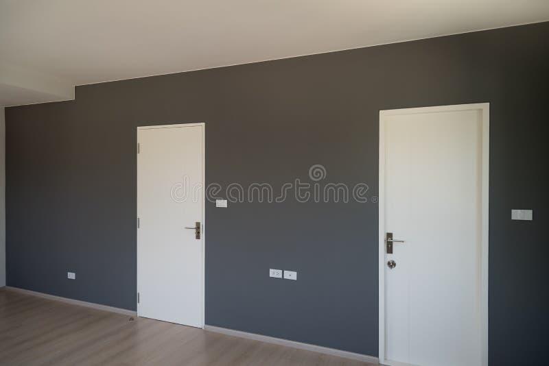 Grijze muurdecoratie met witte gesloten deur stock afbeeldingen