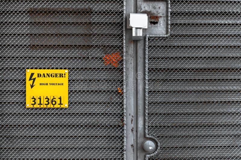 Grijze omheining met geel waarschuwingsbord stock afbeeldingen