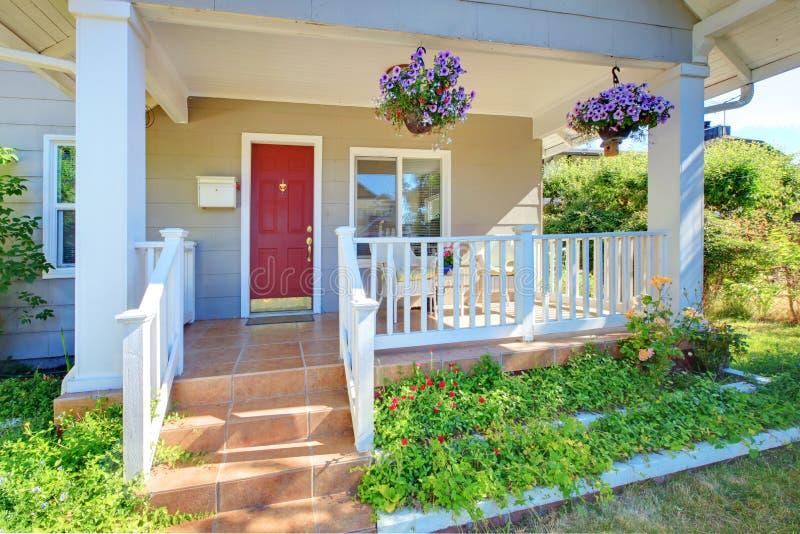 Grijze oude huis voorportiek buiten met rode deur. royalty-vrije stock afbeeldingen