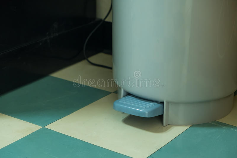 Grijze plastic vuilnisbak met pedaal op groen vloerpatroon royalty-vrije stock afbeelding