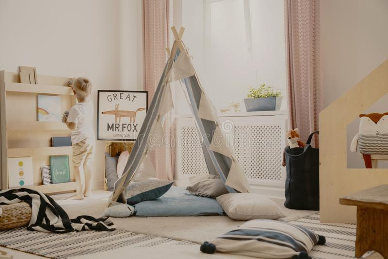 Grijze Skandinavische tent en hoofdkussens in comfortabel speelkamerbinnenland met dekens en houten meubilair, echte foto royalty-vrije stock afbeelding