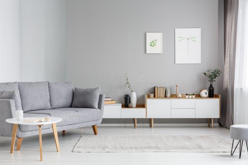 Grijze sofa dichtbij witte kast in minimaal woonkamerbinnenland stock foto