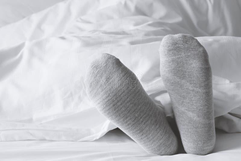 Grijze sokken die op het witte bed ontspannen royalty-vrije stock foto's