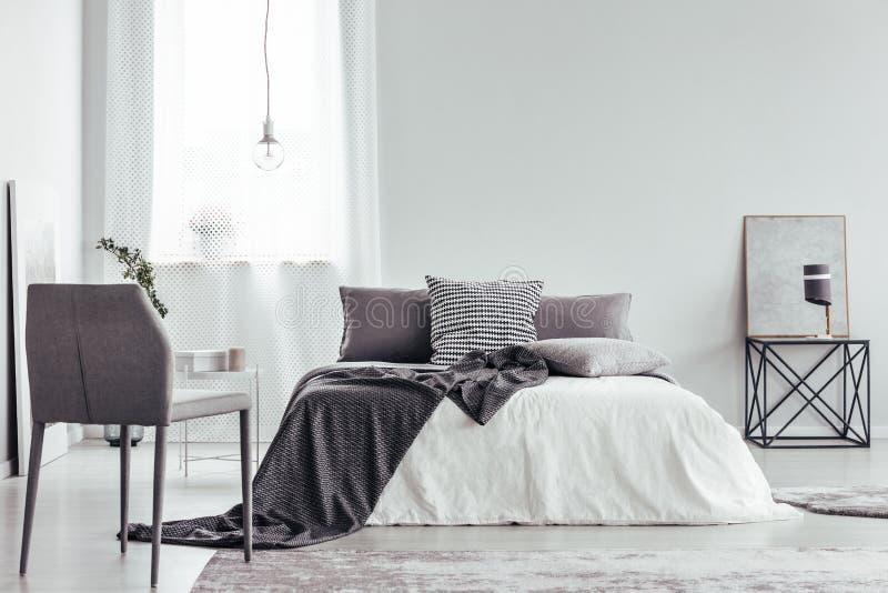Grijze stoel in witte slaapkamer stock afbeeldingen
