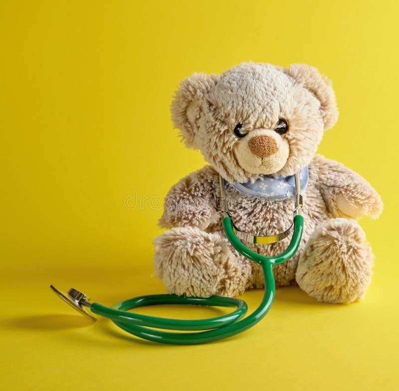 grijze teddybeer en groene medische stethoscoop op een gele achtergrond stock foto
