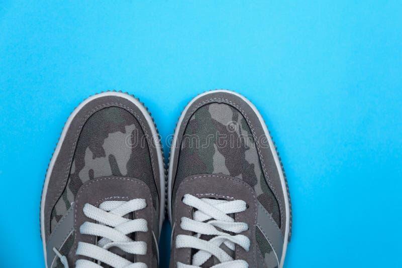 Grijze tennisschoenen op een blauwe achtergrond stock foto