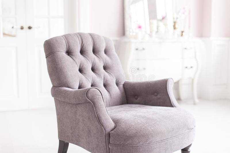 Grijze uitstekende stoel in luxueuze binnenlands van de woonkamer Zachte nadruk stock fotografie