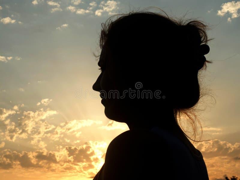 年轻gril剪影在阳光下 免版税图库摄影